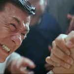 Kuo tries to gain face by winning an arm wrestle