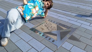Posing with Jackie Chan's hand prints on the Hong Kong Avenue of Stars
