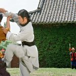 As Yun Fei fights the bodyguards a young Yuen Wah looks on